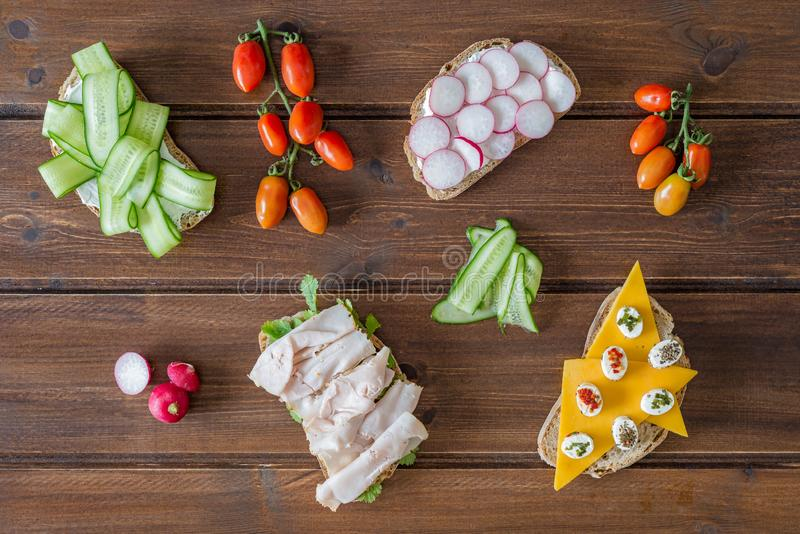 Healthy open sandwiches with vegetables ,cucumber radish turkey pastrami cheddar cheese and soft cheese on wooden background stock photography