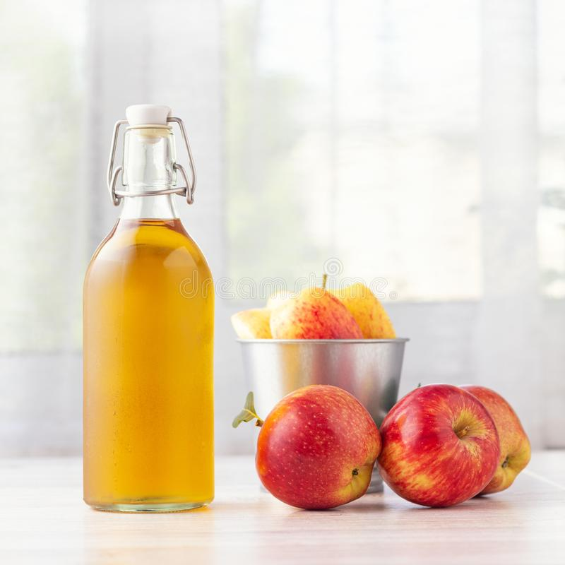 Healthy organic food. Apple cider vinegar or juice in glass bottle and fresh red apples stock image