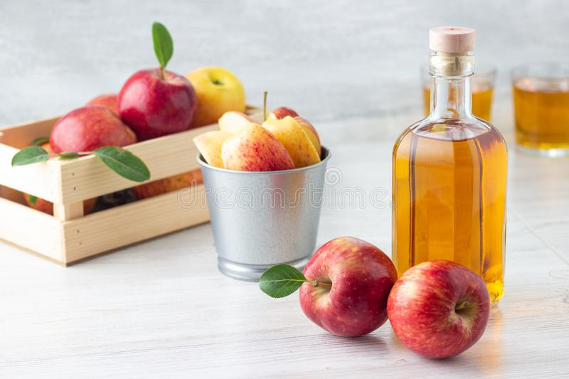 Healthy organic food. Apple cider vinegar or juice in glass bottle and fresh red apples. royalty free stock image