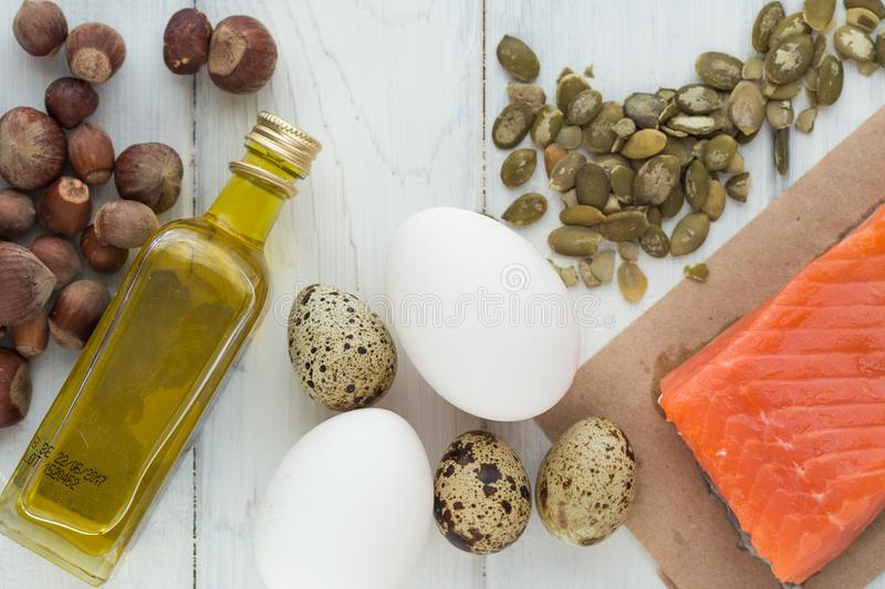 Healthy organic food. Products with healthy fats. Omega 3 omega 6. Ingredients and products: trout salmon olive oil avocado nuts. Cheese eggs. On dark stone stock image