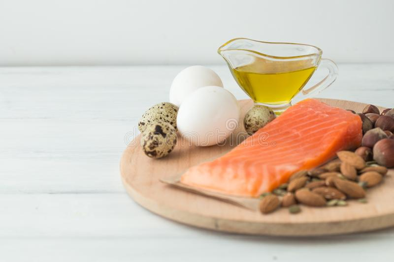 Healthy organic food. Products with healthy fats. Omega 3 omega 6. Ingredients and products: trout salmon olive oil avocado nuts. Cheese eggs. On dark stone stock photography