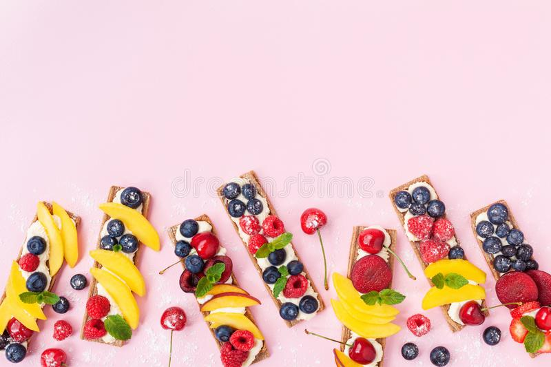 Healthy and organic food snack or dessert from sandwiches with creamy cheese and summer berry fruits on pink trendy background stock images