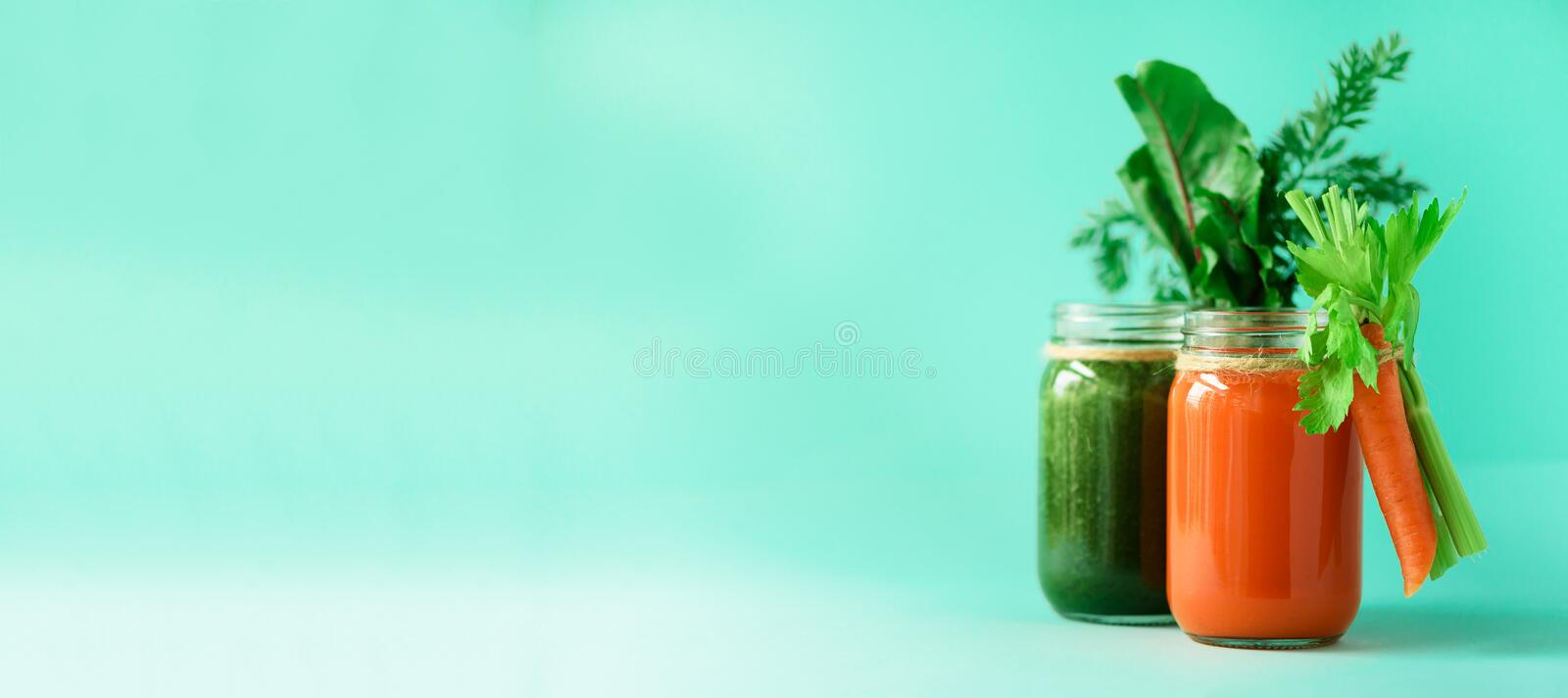 Healthy organic green and orange smoothies on blue background. Banner. Detox drinks in glass jar from vegetables -. Carrot, celery, beet greens and tops. Copy royalty free stock images