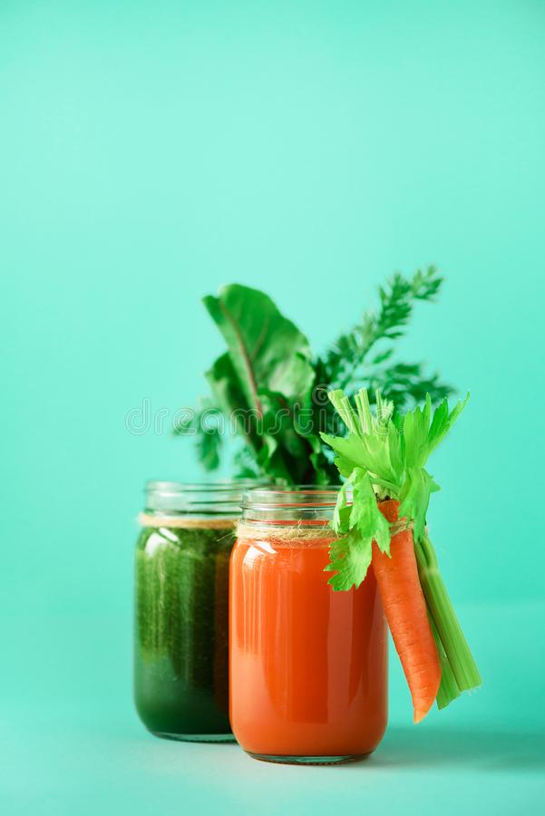 Healthy organic green and orange smoothies on blue background. Detox drinks in glass jar from vegetables - carrot. Celery, beet greens and tops. Copy space royalty free stock image