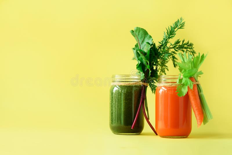 Healthy organic green and orange smoothies on yellow background. Detox drinks in glass jar from vegetables - carrot. Celery, beet greens and tops. Copy space royalty free stock image