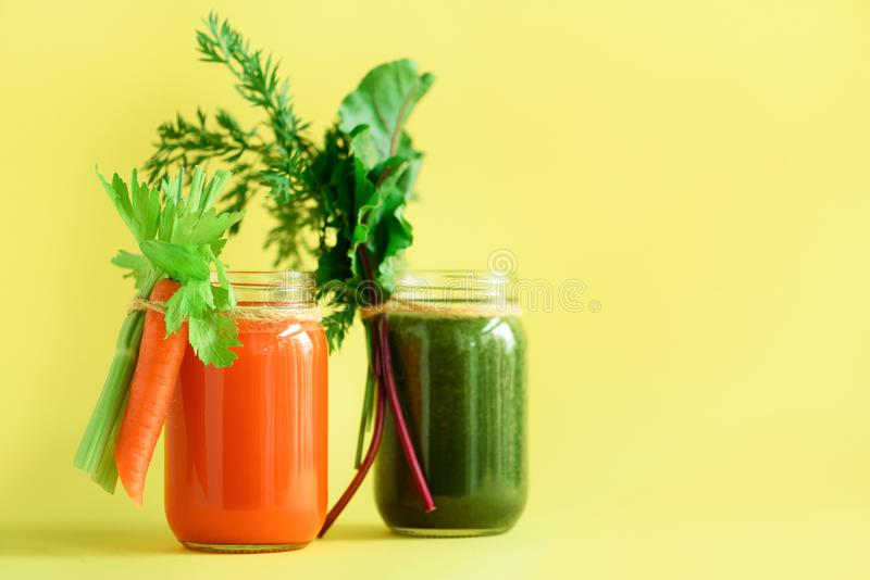 Healthy organic green and orange smoothies on yellow background. Detox drinks in glass jar from vegetables - carrot. Celery, beet greens and tops. Copy space stock photos