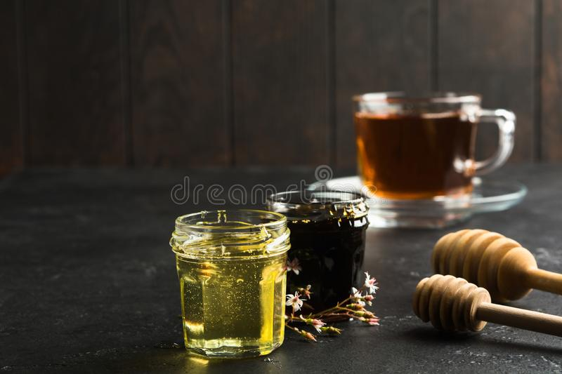 Healthy organic natural food for treatment for colds. Dark and light honey in glass jars on black stone background stock image