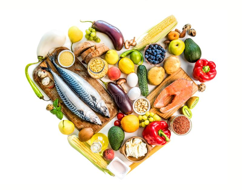 Healthy organic nutritious diet. Plenty of foods on the wooden white table in the form of the heart royalty free stock photography