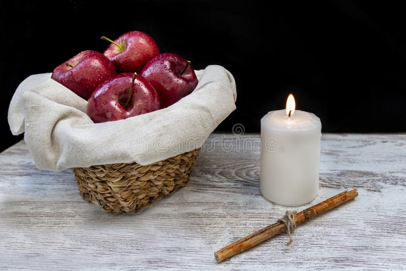 Healthy and organic red apples in a wicker basket, a white candle and a stick cinnamon on rustic background. With copy space royalty free stock photography