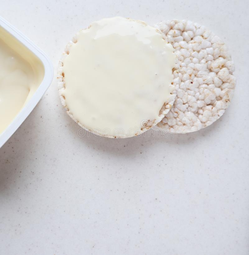 Healthy organic rice cakes with cream cheese on white marble.  stock photo