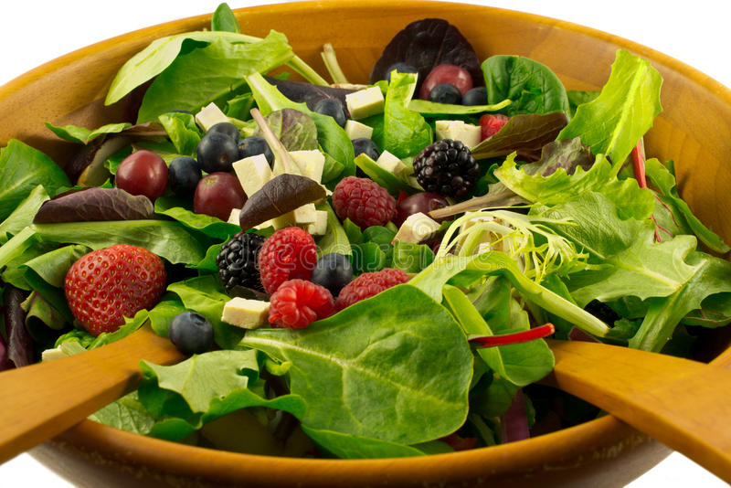 Healthy organic salad. Organic mixed greens, berries and sprouted tofu salad served in wooden bowl, on white background stock images