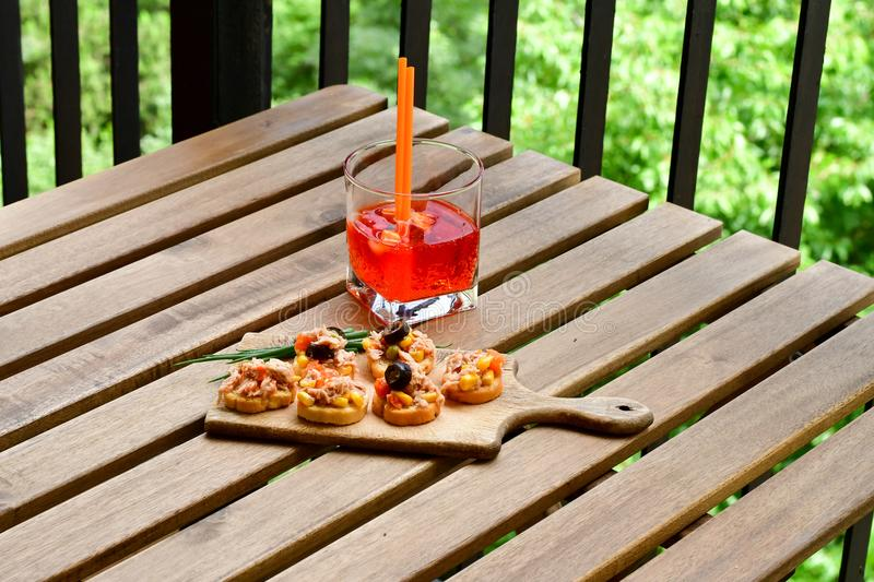 Aperol Spritz. Healthy organic sandwich with bruschetta,Sweet corn , carrots, black olives and fresh onion and grissini and Aperol Spritz royalty free stock image