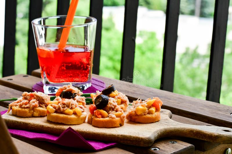 Aperol Spritz. Healthy organic sandwich with bruschetta,Sweet corn , carrots, black olives and fresh onion and grissini and Aperol Spritz stock photography