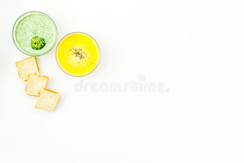 Healthy organic vegetarian meal. Cream soup concept. Soups with pumpkin and broccoli on white background top view copy royalty free stock photo