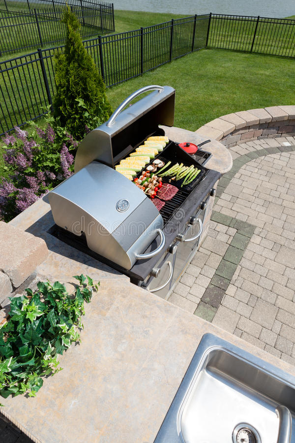 Healthy outdoor living cooking in a summer kitchen. Fitted with a sink and counter and large gas barbecue loaded with fresh vegetables and meat on an open-air royalty free stock image