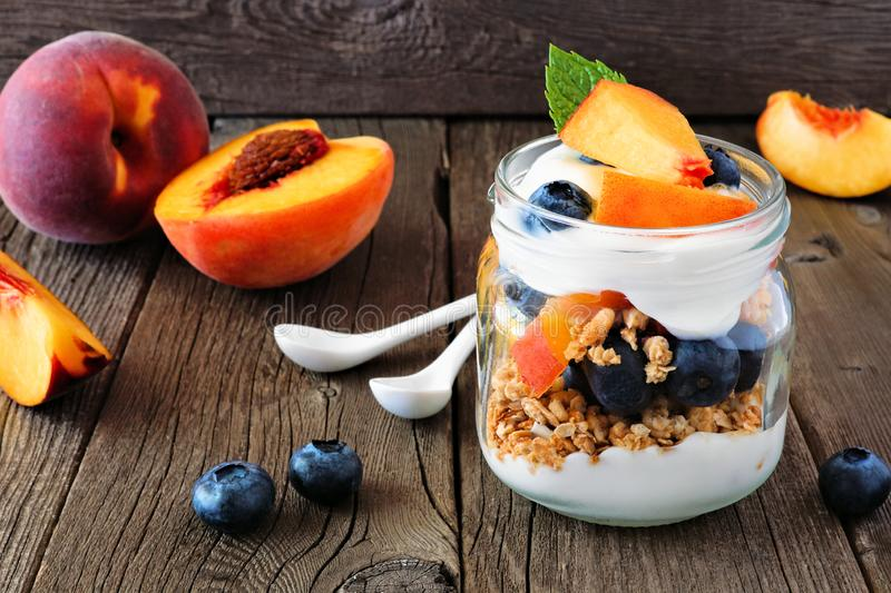 Peach and blueberry parfait in a mason jar on a dark wood background stock image