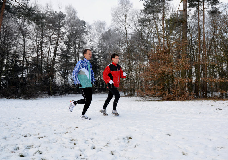 Healthy people running in the snow. Healthy people running in the winter snow stock images