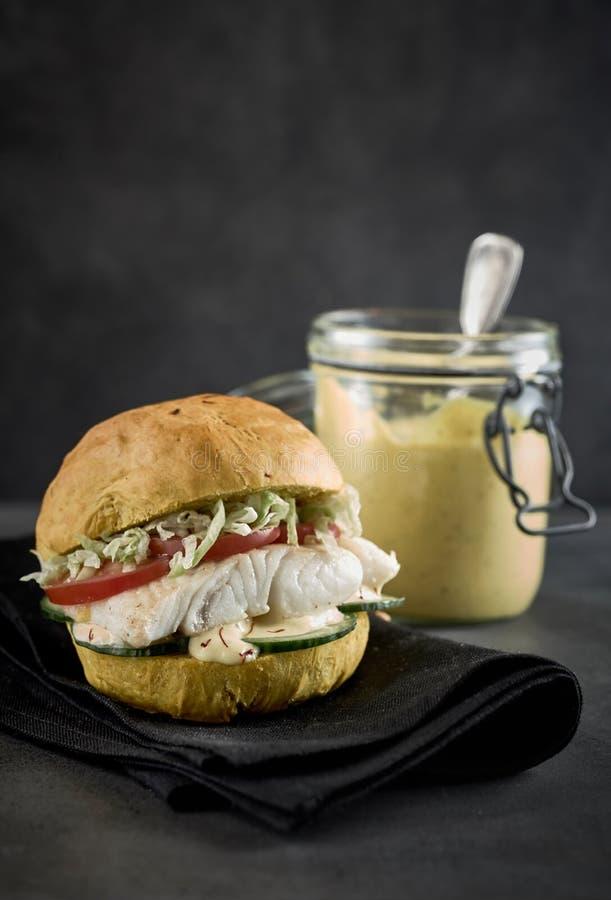 Healthy pollock burger with salad trimmings. Healthy pollock, pollack, coalfish or saithe seafood burger with salad trimmings and a side jar of mayo or tartare stock photography