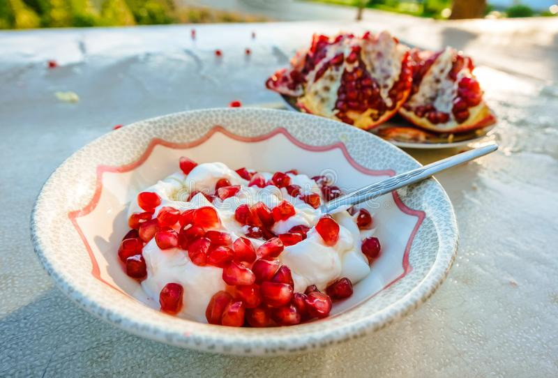Healthy pomegranate and yogurt breakfast on a table outdoors royalty free stock image
