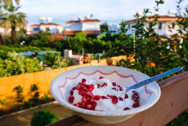 Healthy pomegranate and yogurt breakfast bowl enyoed on the balcony royalty free stock images