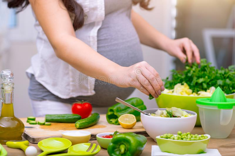 Healthy pregnancy concept. Happy pregnant woman cooking at home, doing fresh green salad, eating many different vegetables during pregnancy, healthy pregnancy stock image