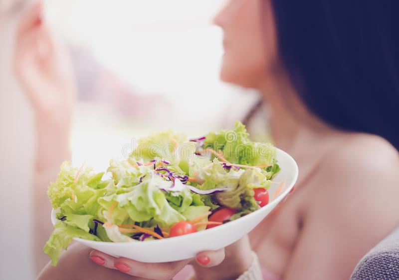 Healthy pretty young woman eating green salad for healthy lifestyle food concept, Asian healthy woman is holding a plate of stock photos