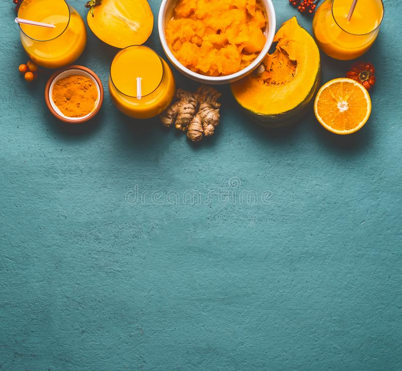 Healthy pumpkin smoothie in glasses with orange color ingredients : persimmon , orange fruits, ginger and turmeric powder on blue stock photo