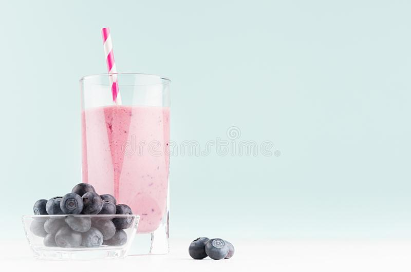 Healthy purple cocktail with blueberry in bowl, striped straw in elegant modern kitchen interior in light soft pastel green color. Healthy purple cocktail with stock images