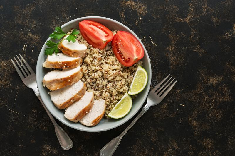Healthy quinoa food with chicken fillet and tomatoes on grunge brown background. Top view, copy space. Healthy eating concept. royalty free stock image