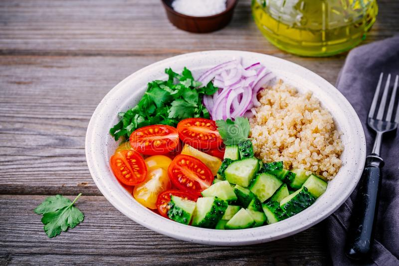 Healthy Quinoa Tabbouleh Salad bowl with fresh cucumbers, tomatoes and red onions royalty free stock images