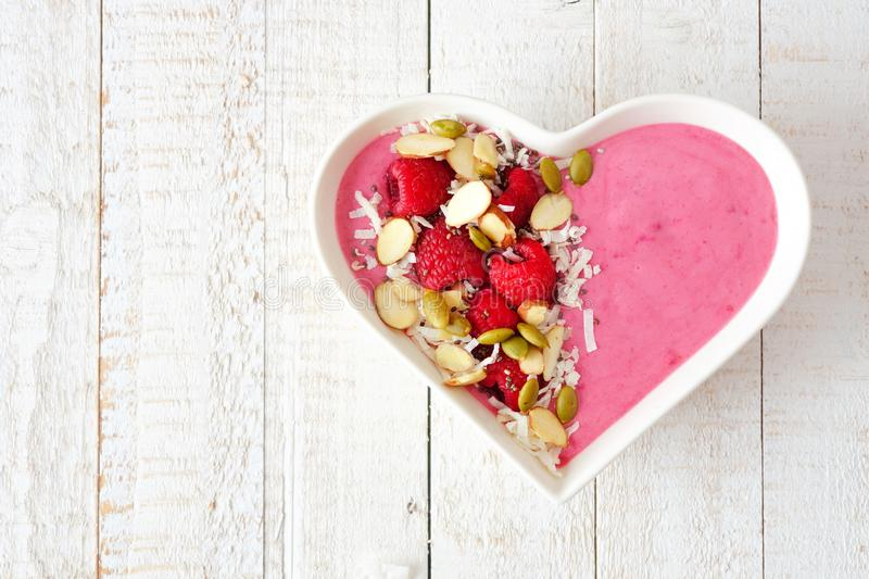 Raspberry smoothie in a heart bowl with superfoods over white wood. Healthy raspberry smoothie in a heart shaped bowl with superfoods. Above view on white wood stock photography