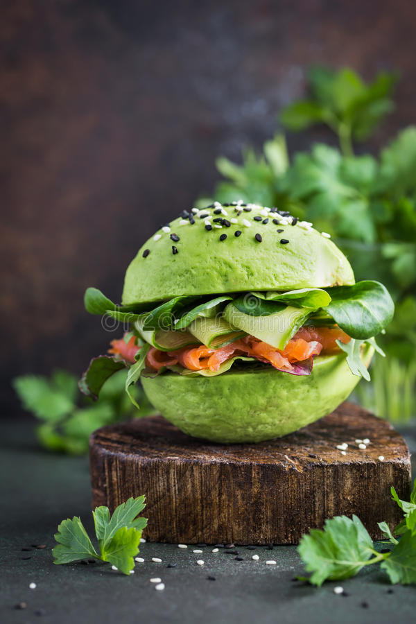 healthy raw avocado burger with salted salmon and fresh vegetables. selective focus stock images