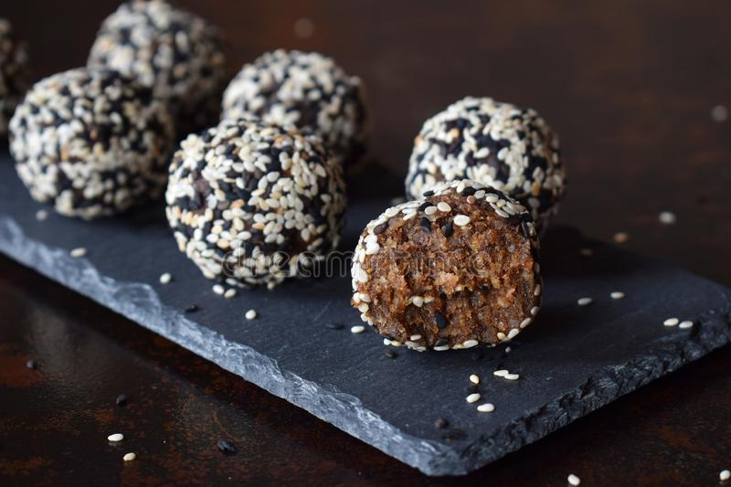 Healthy raw energy bites with flax seeds, almonds, banana and dates. Vegan truffles in sesame seeds on dark background. Homemade stock photography
