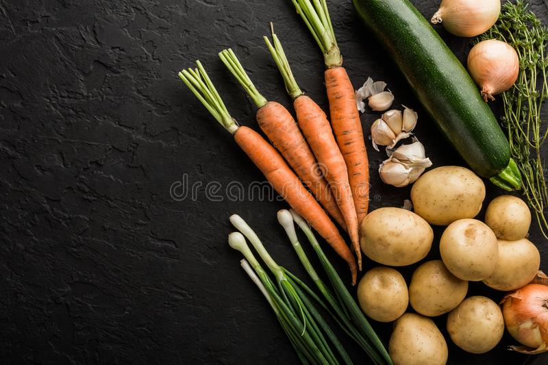 Healthy raw summer vegan vegetables and herbs, carrots, potatoes, zucchini, onion on dark stone background. royalty free stock photography