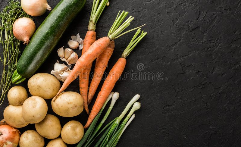 Healthy raw summer vegan vegetables and herbs, carrots, potatoes, zucchini, onion on dark stone background. Healthy food, clean eating, top view, flat lay stock image