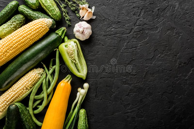 Healthy raw summer vegan vegetables and herbs, cucumbers, corn, pepper, zucchini, green beans on black stone background royalty free stock images
