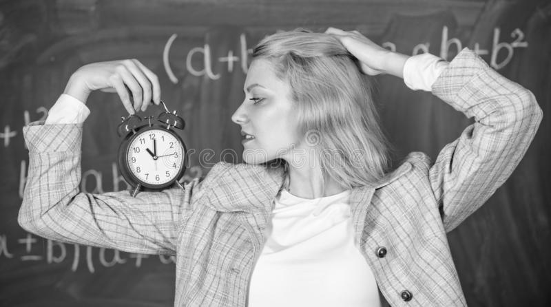 Healthy daily regime. Educator start lesson. She care about discipline. Woman teacher hold alarm clock. Lessons schedule stock image