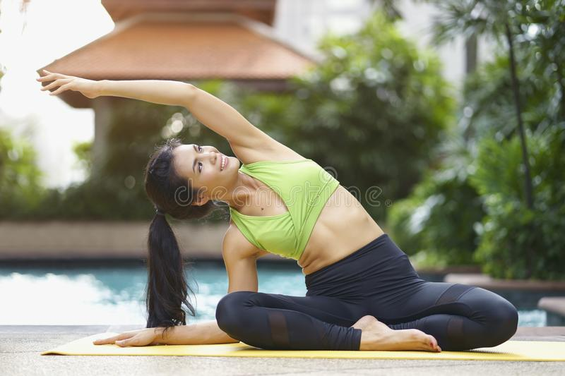 Healthy and Relaxation concept. Happy asian woman practicing yoga pose or pilates and sitting near swimming pool royalty free stock photos