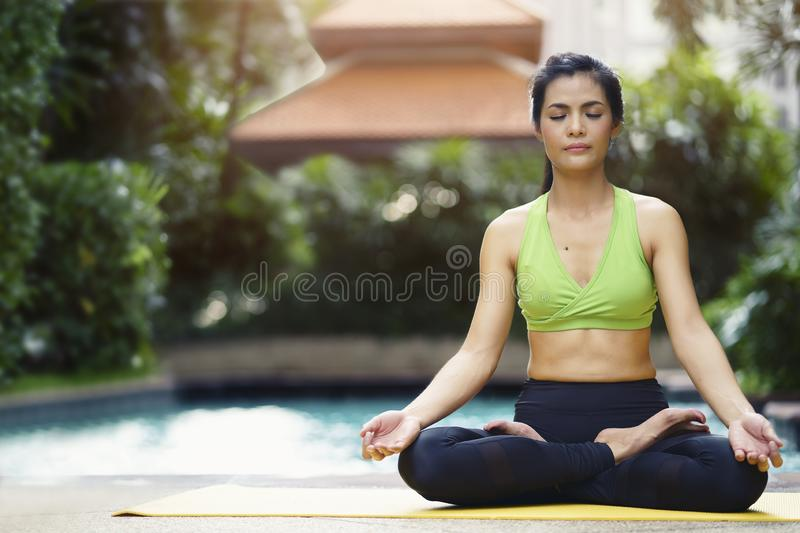 Healthy and Relaxation concept. Woman practicing yoga pose meditates in the lotus position sitting near swimming pool. stock photo