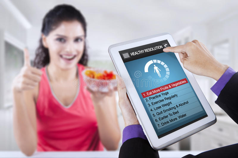 Healthy resolutions app with woman holds tomato royalty free stock photos
