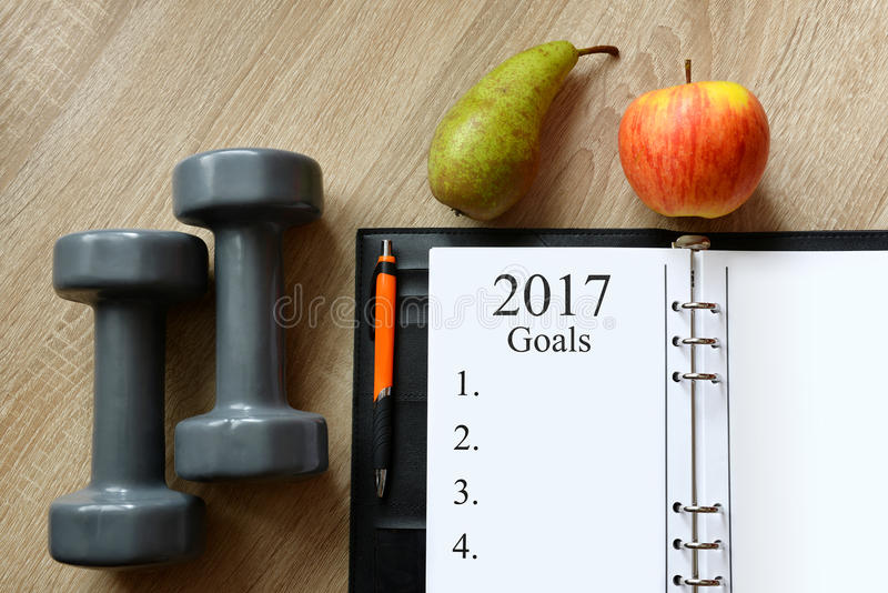 Healthy resolutions for the New Year 2017. Dumbbells with fruits and open notebook on wooen desk. Healthy resolutions for the New Year 2017 royalty free stock photography