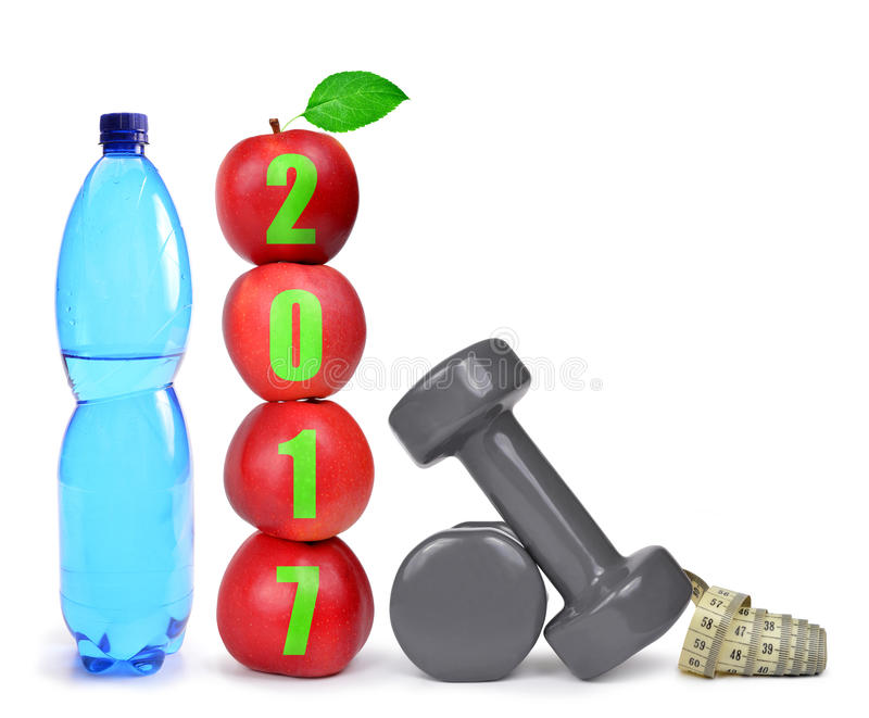 Healthy resolutions for the New Year 2017. Red apples, dumbbells and PET bottle with drinking water on white. Healthy resolutions for the New Year 2017 stock photo