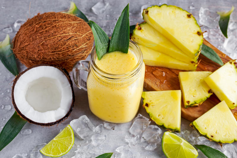 Healthy ripe Yellow Pineapple, coconut, Smoothie with slices of Lime and ice royalty free stock photos