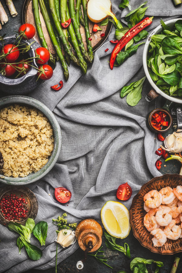 Healthy salad with asparagus and cooked quinoa seeds, preparation on rustic background with various organic vegetables, top view, royalty free stock photo