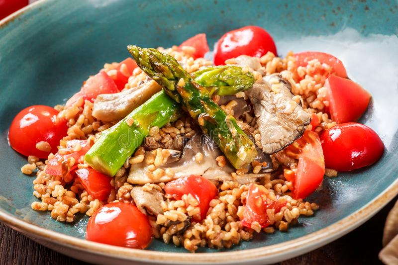 Healthy salad of barley porridge with asparagus, tomatoes and mushrooms on plate. Vegan food. royalty free stock image