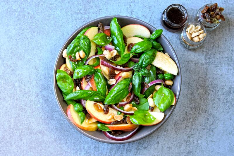 Healthy salad with basil and apple. Salad with apple, raisins and nuts. Vegan bоwl with apple basil and blue onion. Apple salad. Autumn salad with apples royalty free stock photos