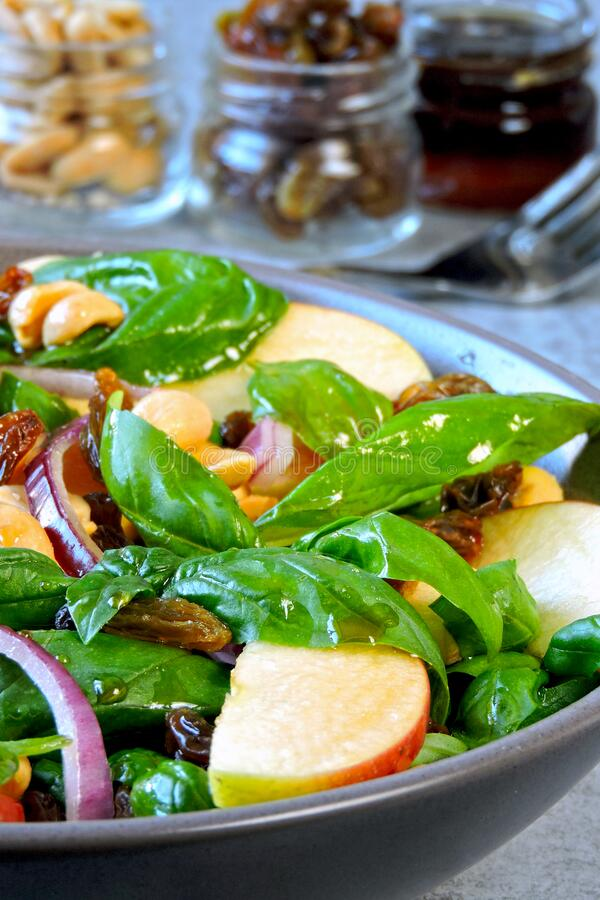Healthy salad with basil and apple. Salad with apple, raisins and nuts. Vegan bоwl with apple basil and blue onion. Apple salad. Autumn salad with apples stock photography