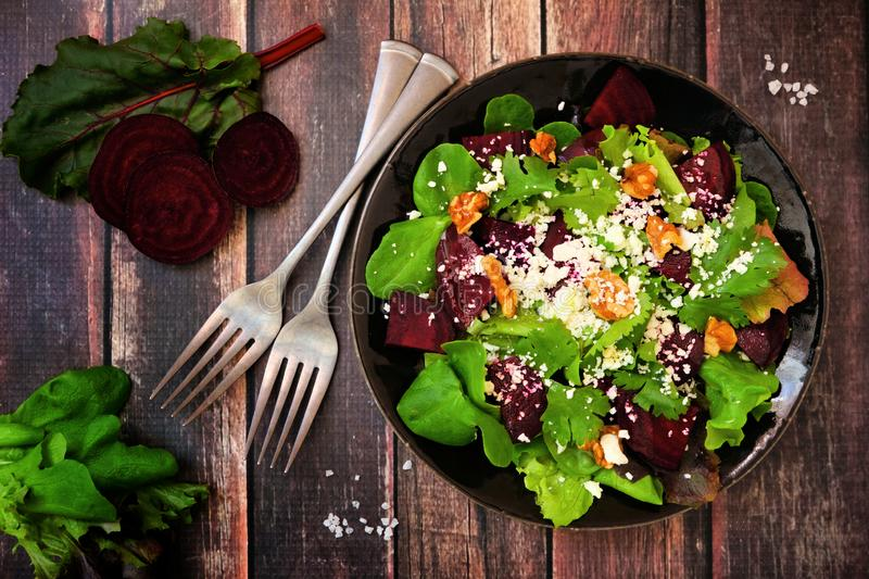 Healthy salad with beets, mixed greens, carrots and feta cheese, above view scene against wood royalty free stock photo