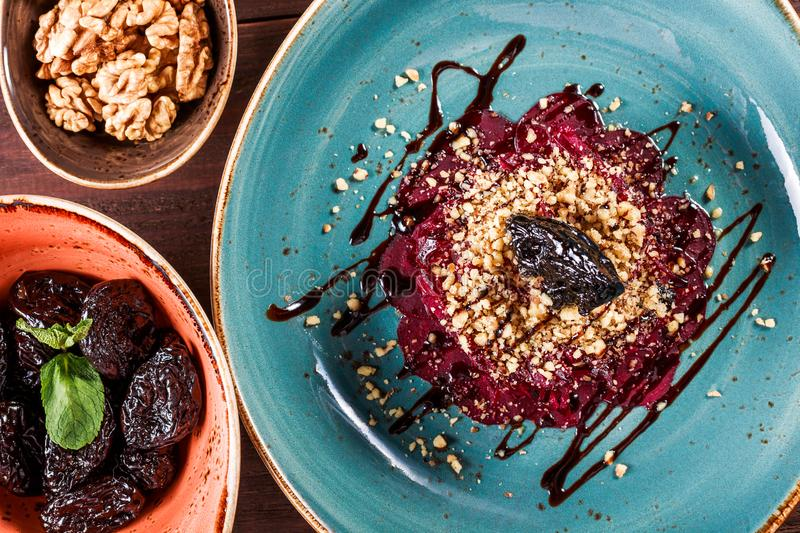 Healthy salad of beets, prunes and nuts on wooden background. Vegan food. stock images