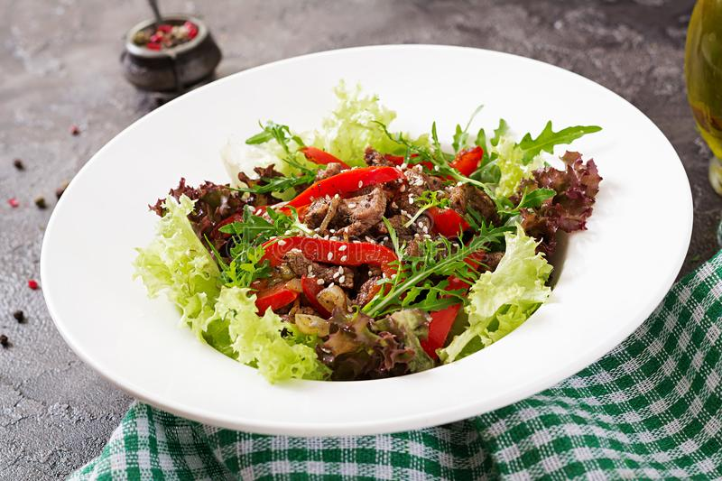 Healthy salad bowl with beef meat, sweet peppers, onions and mixed greens stock images
